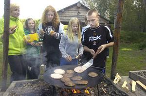 Lunchdags och Fredrik Lans ser till att hamburgarna blir ordentligt stekta.