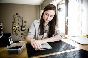 Frida Lindberg börjar på en ny pärlplatta och lägger snabbt upp en svart rad.