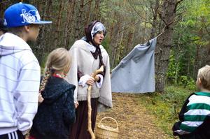 Gertrud (Mari Andersson-Jansson) berättar för eleverna om äventyret som väntar när de passerat den magiska tidsporten.