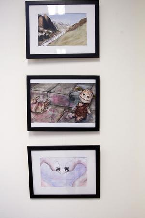 Fler av Jenni Funges konstverk. Överst hänger en landskapsbild, tavlan i mitten föreställer en docka, den nedersta visar två svanar.