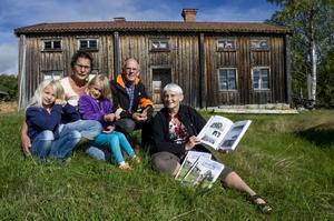 Bokjobbarna Karl-Evert Hellström och Sara-Eva Ögren tillsammans med Lännäs byskoleförenings ordförande Ulla Johansson, t v, och hennes sondöttrar Tilde och Wilma Johansson. Bakom dem syns byns kanske äldsta hus som ännu står,