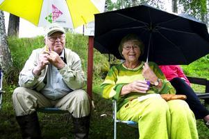 Trivdes trots regnet. Här är det Bertil Mattsson från byn och Laila Nordstedt från Smedjebacken som njuter av tillvaron på hyttbacken skyddade under sina paraplyer. Foto:Karin Rickardsson