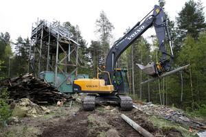 Rivningen av hoppbackarna på Kvarnberget har startat. Den mindre backen i trä är först ut. Erik Gustafsson i grävskopan har full kontroll.