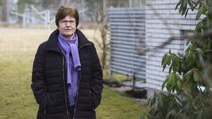 """Christine Larnhed i Uggelbo bor granne med platsen där äldreboendet föreslås (i bakgrunden). """"Jag blir förvånad om de tar bort möjligheten att vistas på planen"""", säger hon."""