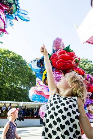 Elly Enberg pekar på ballongen hon vill ha, i bakgrunden syns lillasyster Ines som funderar lite längre på vilken ballong som är finast.