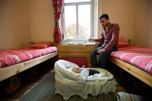 Det är dags för lunch och Moataz Amino har fått upp en matlåda från köket i Gärdshyttan. På golvet har lille Hamza precis vaknat i sin korg.