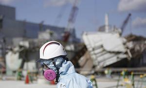 En arbetare i skyddsmask vid det drabbade kärnkraftverket.