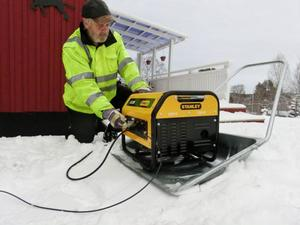 Gunnar Frändegård räddar köttvarorna i frysen med inlånat reservaggregat uppställt på snöskyffel, intill hemmet i Åsgård.