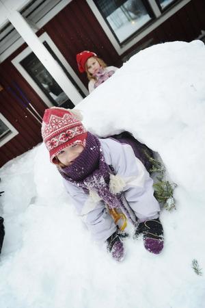Eira tycker om att leka i snögrottan på gården. Hanna (i bakgrunden) också.