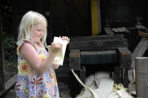 Alva Holm, 7 år, fick lära sig att spånen från den stora maskinen användes till tak förr i tiden.