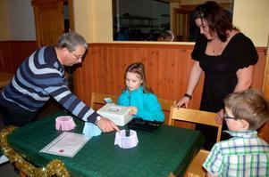 Elina Forsgren, 8 år, här tillsammans med mamma Maria Aronsson och lillebror Erik säljer lotter till Per-Arne Bergström.