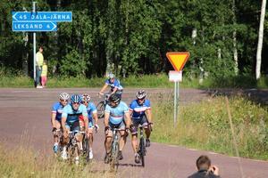 En blå kedja av cyklister i strålande sommarsol under loppet.