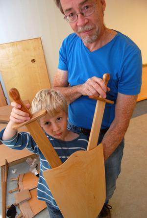 Micael tillsammans med sin visar en leksak som han till tillverket. En sköld med träsvärd.