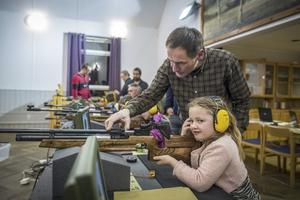 Lägg an. Stefan Törnqvist hjälper Tilda Lönnqvist, 6 år, att ladda. Sedan uppmanas hon att ha båda armbågarna stadigt på bordet, ha blicken stilla framåt. – Och krama sakta av, säger han.