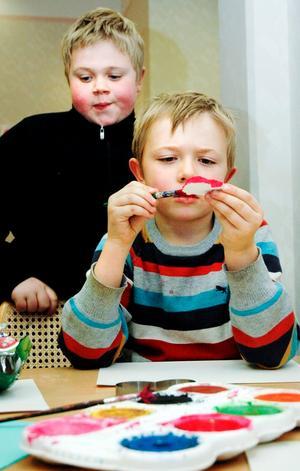 William Berg målar ett hjärta till sin pappa. Storebror Samuel tittar på.