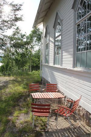 En trädgårdsmöbel har fått flytta redan i förväg och står och väntar nedanför de höga fönstren.