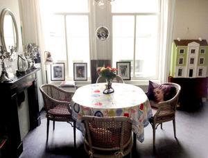 Matbordet viktigaste möbeln. Discobollen i matrummet med tillhörande spotlights i flera färger används flitigt till frukost. Matbordet fälls ofta ut och då ryms där mellan 12 och 15 personer. I den gemensamma trädgården bor en koloni förrymda papegojor. När hon öppnar fönstren låter det som en tropisk djungel utanför.