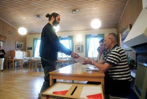Pär Hansson från Täng i Ås röstade i församlingshemmet vid kyrkan i Ås. Han lämnade sitt röstkort och sin röst till Nils Gunnar Nilsson. Valfunktionärerna bortom honom är Tomas Sjövall och Ingrid Torstensson, och i dörröppningen Kristin Sahlin.