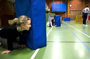 Maria Signell gömmer sig bakom en madrass under gymnasternas
