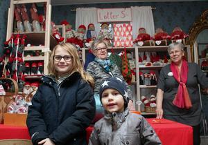 Stella och Olle Lyxell har sett fram emot lotteriet på julmässan. I bakgrunden Ulla-Britt Andersson och Kerstin Persson, Folkärna Hembygdsförening.