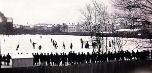 Bandy på Gamla plan. E.W. Krassing har fotograferat Gamla plan söderifrån någon gång runt 1930. Publiken står på snövallarna. Planen stängdes 1931 när Arosvallen invigdes. Herrgärdsskolan syns överst till vänster.