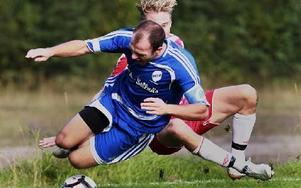 FOTBOLLSDANS. Planens bäste spelare, Ulfshyttans Johan Wedberg, valsar runt med en motståndare.Foto: STAFFAN BJÖRKLUND