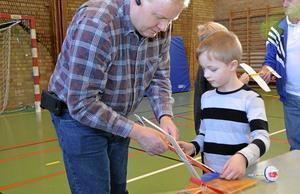 Sjuåriga Daniel Henningsson får hjälp av pappa Bo med att spänna gummisnodden som får propellern att snurra på flygplanet.