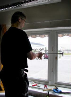 Lasse Österman i färd med att spärra fönstren på ett av kommunens förvaltningskontor med stadiga galler.