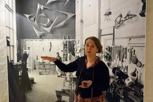 Curator Maria Sundström framför John Wahlbärjs stora fotografi av Arne Jones i ateljén.