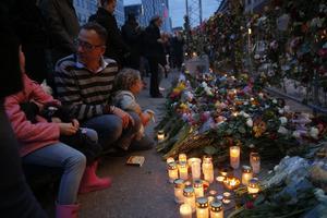 Människor och blommor till minne av offren i fredagens terroristattack på Drottninggatan.