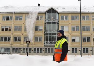 Jocke Svedberg står och håller vakt medan kollegorna skottar på taket.