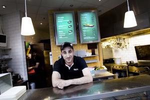 Serdar Bardakci har fått en heltidsanställning på Nians husmansrestaurang och är glad och nöjd när några av stans centerpartister hälsar på för att prata sänkt restaurangmoms.