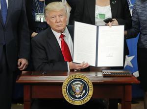 USA:s president Donald Trump håller upp orden om skärpta regler för invandring och byggandet av muren som han signerade i Washington på onsdagen.