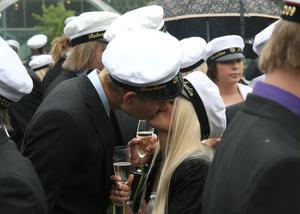 Molly Östlin och Markus Åsberg firar studenten med en kyss.