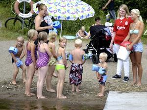 Lek på gång. Barnen som badade vid Sågviken var genast med på noterna när Eva-Lena Ströman (i rött) och Sanna Jönsson (längst till höger) föreslog bollek i vattnet.Ny kontakt. Julia Impola Gerlström passar på att få lite extra uppmärksamhet och åktur i vattnet av Sanna Jönsson.