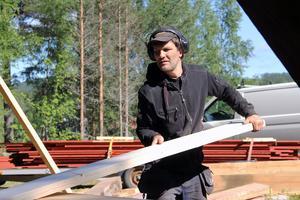 Petter Landin har sågat till virket till nya golvåsar för klockstapeln. I bakgrunden syns det rödmålade virket till den nya panelen.