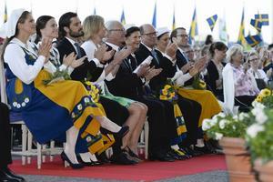 Prinsessan Madeleine, prinsessan Sofia, prins Carl Philip, Jenni Ahlin, kung Carl Gustaf, drottning Silvia, talman Urban Ahlin, kronprinsessan Victoria och prins Daniel vid nationaldagsfirandet på Skansen 2015.