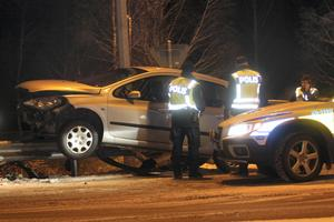 Polisen undersöker bilen som kört upp på räcket.
