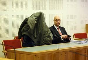 Advokat Kaj Axlund tillsammans med den 40-årige före detta OG-ledaren som står åtalad för stämpling till mord och grov utpressning.