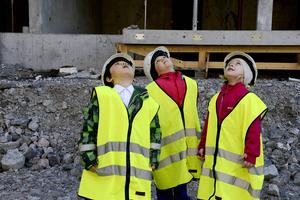 Förskolekompisarna Kevin, Annie och Emilia spanar in byggkranen som sveper genom luften med sin tunga last.