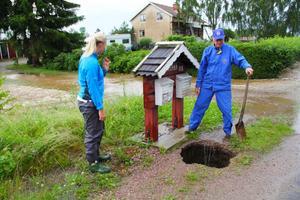Anna Jonasson och Lars-Erik Jonasson tittar till mark som blivit underminerad. Bakom syns huset och den bortspolade gårdsplanen.