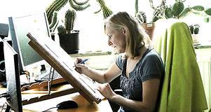 Eija Blomander framför sitt staffli i arbetsrummet.
