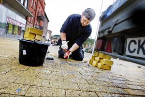Micke Elvbo arbetade förut på Husqvarnas fabrik i Tandsbyn. Nu byter han ut den gula stenen på Stortorget åt Pilgrimstad cementvarufabrik.