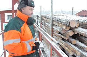Virkesmätaren Jens Thomasson gör en bedömning av mängd och kvalitet på virket innan det lastas av på terminalen.
