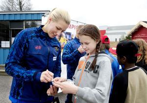 Danijela Rundqvist skriver en autograf åt Freja Persson från Mariedalsskolan