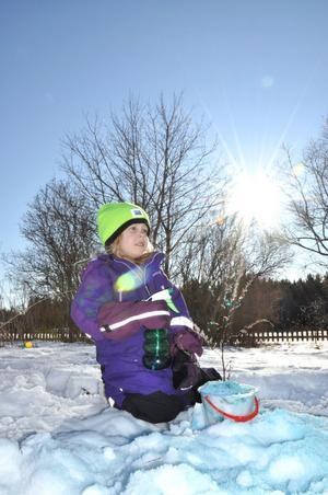 KONSTVERK. Freja Carlsson har byggt en snöslott som hon färgat blått.