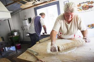 Ingrid Newberg bakar ut tunnbrödet med hjälp av en knottrig kavel för att göra lufthål i degen.
