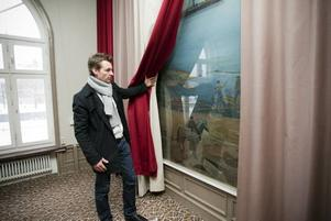 Anders Hedström visar Einar Forseths målning bakom ett draperi. Konstnärens verk pryder även Gyllene salen i Stockholms stadshus.
