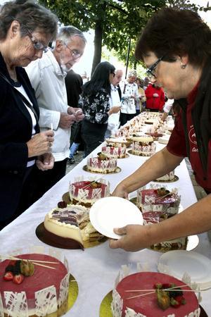 God dag. Kumladagens längsta kö bildades utanför Sveas konditori som firade 70-årsjubileum genom att bjuda på tårta. Här är det Carina Falk som sköter tårtspaden. Bild: JAN WIJK