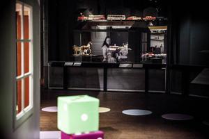 Längs väggarna hittar du montrar med dockor i olika storlekar och modeller, i rummets mitt finns små husmoduler med inredda barnrum. Tack vare spotlights skapas spännande ljuseffekter och återspeglingar i rummet.